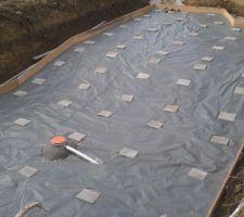 Pose du film polyuréthane, afin de limiter la descente du béton dans le drain.