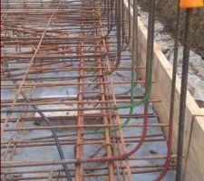 Afin d'améliorer la résistance mécanique, les fers sont positionnés de manière alternée.  1 - Le fer arrière du mur est ligaturé à la nappe de treillis inférieure et le fer avant à la supérieure (repères rouges sur la photo). 2 - Le fer arrière du mur est ligaturé à la nappe de treillis supérieure et le fer avant à l'inférieure (repères verts sur la photo). Nous pouvons également observer sur le bas de cette photo, le raccordement du câble de protection cathodique sur la structure métallique (Voir schéma des mises à la terre). Un câble est raccordé à chacun des angles de la structure. Afin d'assurer une bonne liaison électrique, le fer a été nettoyé à blanc avant raccordement.