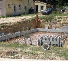 On monte les murs en blocs à bancher. Placement de deux tors de 8 mm à chaque couche avec épingle de liaison aux coins. Les blocs sont collés avec de la colle de carrelage pour éviter tous mouvements en attente du remplissage des blocs.