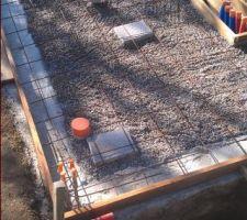 La dalle du local technique prête à être coulée. Nous pouvons remarquer la mise en place d'un siphon de sol pour la partie technique, d'un écoulement de 100 pour les toilettes et d'une longue réservation pour remonter les circuits hydrauliques du bassin. Des fourreaux ont été acheminés à l'extérieur pour les arrivées d'eau (Réseau et pluie), le départ vers la douche solaire, l'arrivée générale d'électricité et le départ pour l'éclairage extérieur.