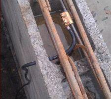 Comme à l'occasion de la réalisation du radier. 4 câbles sont acheminés près des angles du bassin pour raccordement sur le ferraillage. Ils permettront une bonne équipotentialité de l'ensemble, en vue du système de protection cathodique précédemment décrit. Les raccordements seront protégés par de la bande d'étanchéité avant le coulage du béton.
