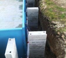 Le tuyau de drainage fait le tour de la piscine. Les parpaings sont montés autour de la piscine à intervalles réguliers en vue de servir de soutien à la future dalle pour la plage.