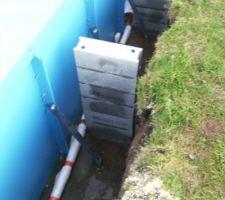 Vue du tuyau de drainage entouré d'un film géotextile, des panneaux fixés au sol et des jambes de force.