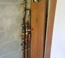 Circuits d'eaux dans le local technique. En bas, de gauche à droite, l'arrivée en eau de pluie (depuis le circuit existant dans l'abri de jardin) ; l'arrivée en eau du réseau ; départ vers la douche solaire.