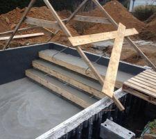 Réalisation de l'escalier maçonné avec plage immergée sur la largeur de la piscine.