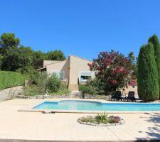 Vue générale de la piscine et  terrasse avec en fond la maison