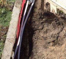 Mise en place des tuyaux souples, j'ai fait les traversées avec du PVC 63 pour servir de fourreau, scellé avec de la mousse. L'électricité est aussi tirée en attente pour le volet roulant et le forage