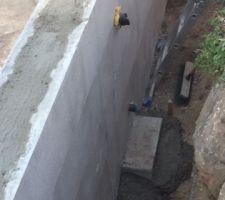 Mise en place d'agglos en pied de traversée,pour réduire les descentes et la profondeur des tuyaux (bonde latérale et prise balai)
