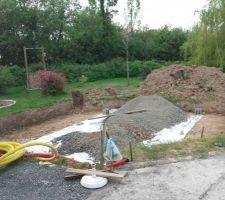 La piscine semi-enterrée est creusée. Un gros tas de concassé attend d'être étalé sur une toile géotextile.