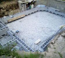 Gravier répartis sur toute la surface de la piscine et les 2 premiers rangs de bloc à bancher installés sur des plots. Les ferraillages de reprise entre la dalle et les murs sont également installés au fur et à mesure.