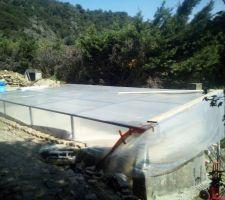 Une protection du bassin pour pouvoir réaliser l'enduit de finition sans être pollué par l'extérieur. Il s'agit du structure mécano-soudée recouverte d'une bâche transparente.  La petite piscine est maintenat installée à l'extérieur du bassin.