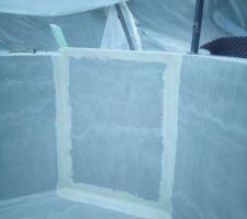 Renfort des angles avec de la toile de verre noyée dans l'enduit de finition.