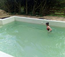 Piscine remplie. Le niveau est volontairement bas, car il ne s'agirait pas que l'eau déborde dans le bac tant qu'il n'est pas terminé. L'eau de source utilisée pour remplir la piscine donne une couleur légèrement verte à la piscine. Mais heureusement, ça va disparaitre.