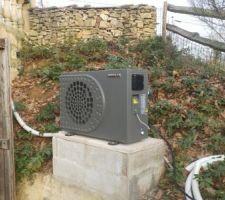 La pompe à chaleur POOLEX Inverter en place près de l'entrée du local technique enterré et en cours de raccordement.