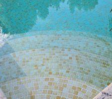 La piscine est carrelée en petite faience jaune.