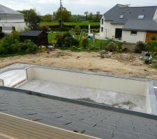 La dalle de béton a été faite autour de la piscine et les margelles sont posées