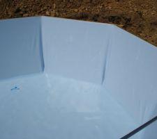 Il est impératif de faire disparaître les plis du fond avant qu'il y ait plus de 5cm d'eau. Après c'est trop tard. Au cours du remplissage, mettre en place les contres bride des buses, spot et skimmer dès que l'eau arrive juste en dessous. Puis découper le liner au centre.
